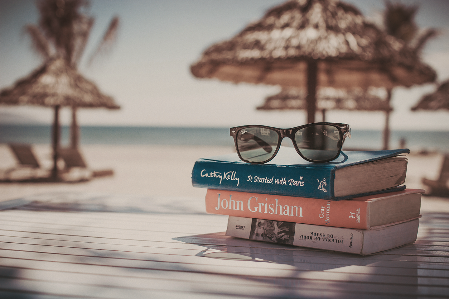 Vacation photo by the beach, sunglasses and books